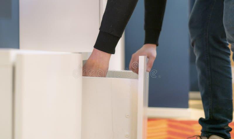 Nahe hohe Hand öffnet das Schlafzimmer des Regals zu Hause, das nach Sachen f sucht stockbild