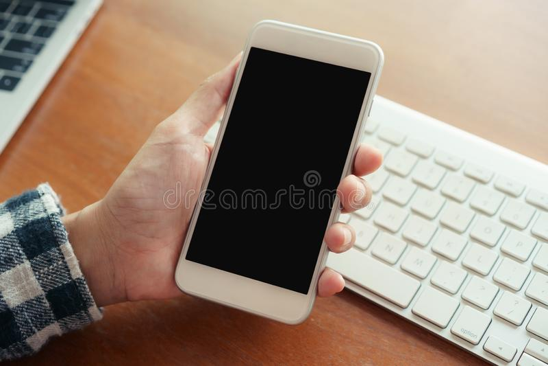 Nahe hohe Hand unter Verwendung des Smartphoneschreibtischhintergrundes im Büro An Hand Halten der leeren Anzeige des Smartphone stockfotos
