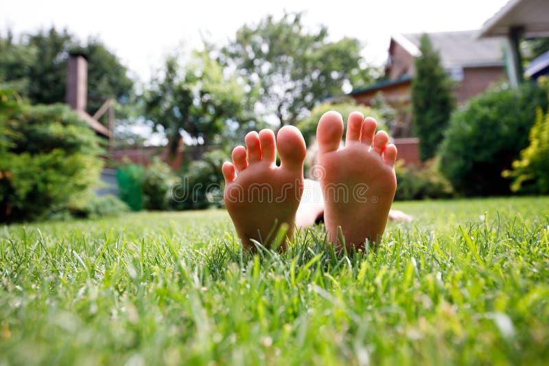 Nahe hohe Kinderfüße auf grünem Gras lizenzfreie stockfotos