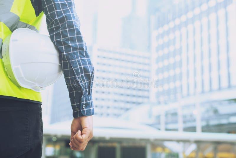 Nahe hohe Rückseitenansicht der Technik des männlichen Bauarbeiterstands, der weißen Sturzhelm der Sicherheit hält lizenzfreie stockfotografie