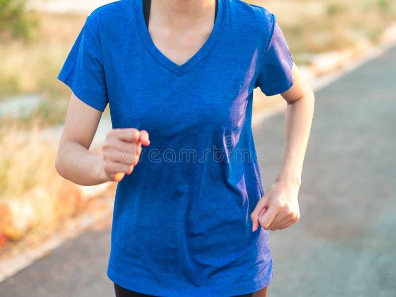 Nahe hohe Weichzeichnung des Laufens der jungen Frau im Freien im Park stockbilder