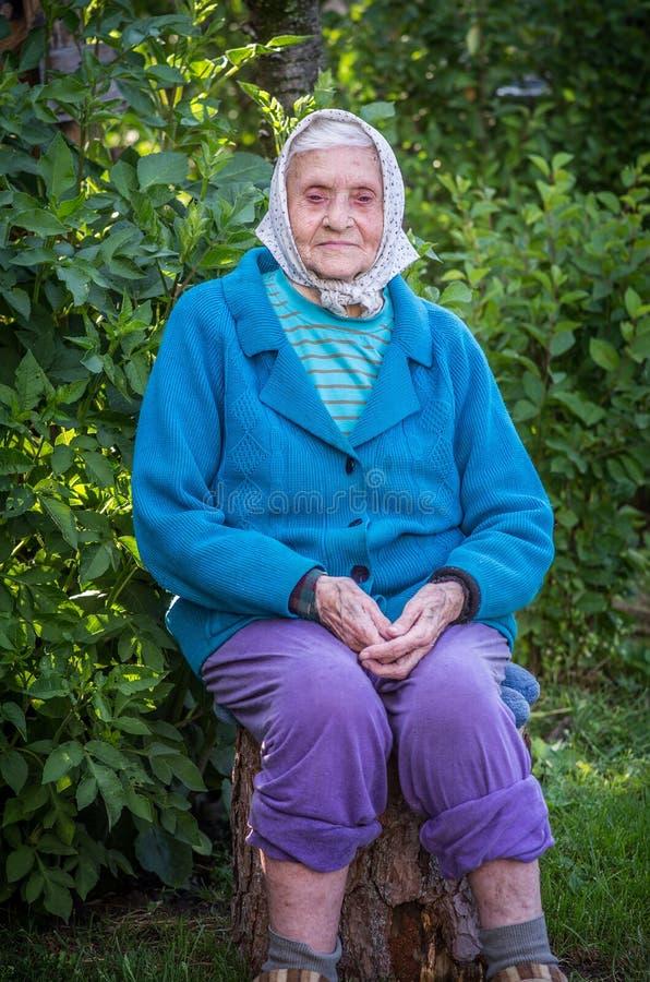 Nahe hundert Jahrfrau, die draußen sitzt lizenzfreies stockbild