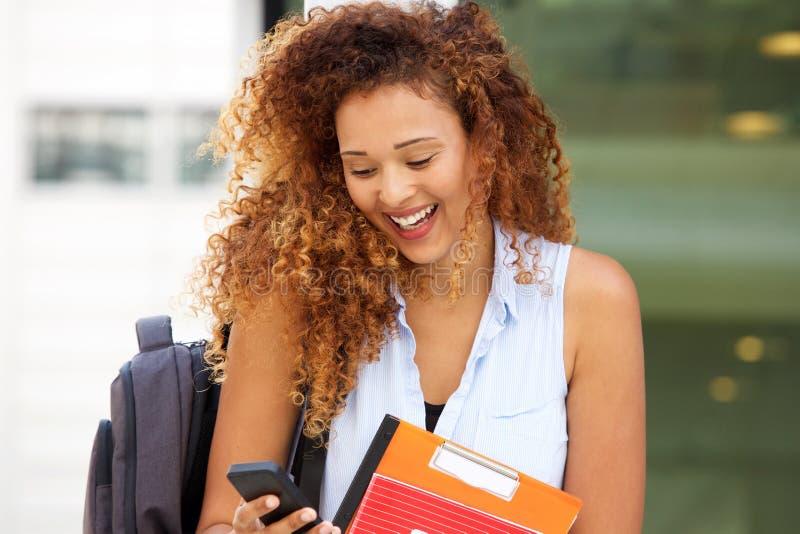 Nahe oben glückliche Studentin mit dem gelockten Haar, das Mobiltelefon betrachtet stockfotografie
