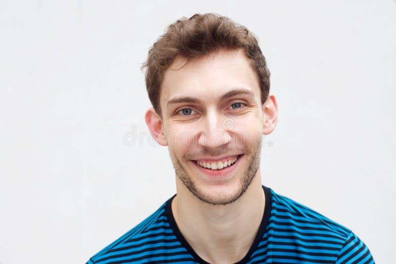 Nahe vor dem gut aussehenden jungen Mann, der vor isoliertem weißem Hintergrund lächelt lizenzfreie stockbilder