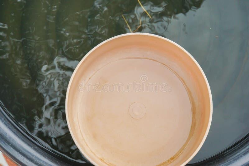Naher alter traditioneller Plastikwasserschöpflöffel im Plastikbecken lizenzfreie stockfotografie