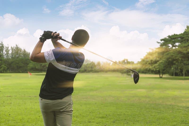 Naher hoher Golfspieler fährt Golfball zum grünen Kurs mit hellem Aufflackern lizenzfreies stockfoto