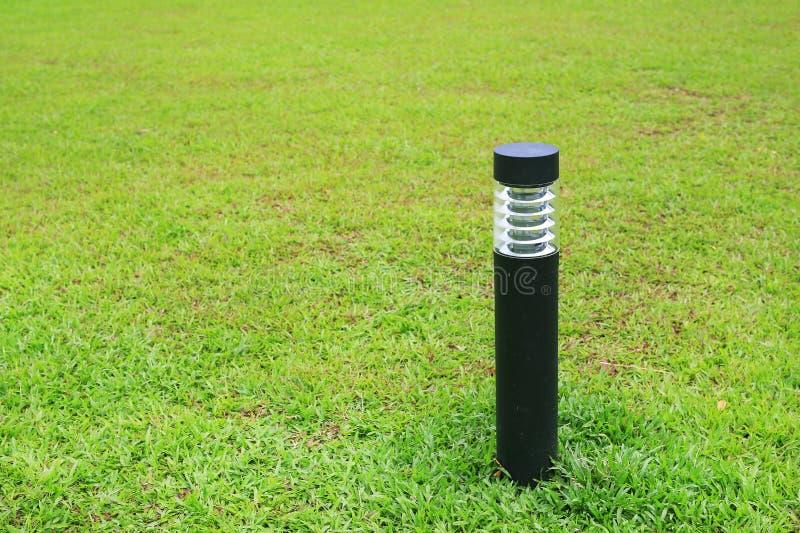 Naher hoher Pfosten der Lampe in der grünen Rasenfläche stockbilder