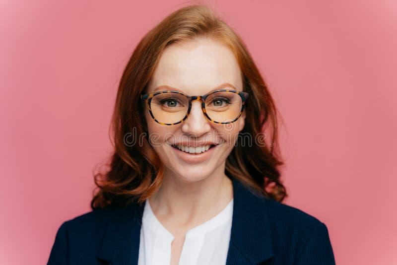Naher hoher Schuss der herrlichen Frau der schönen Rothaarigen in den optischen Gläsern, hat das toothy Lächeln, gekleidet in der lizenzfreie stockfotografie