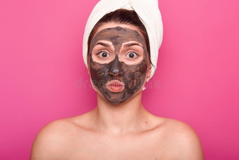 Naher hoher Schuss der schönen Frau, hat Schokoladenmaske auf Gesicht, hält Augen sich öffnete weit und Lippen rundeten, Haltunge stockfotos