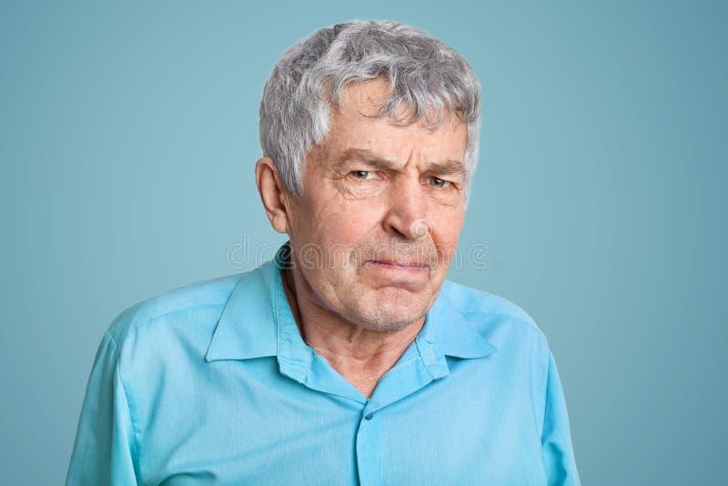 Naher hoher Schuss des älteren Mannes mit Falten auf Gesicht, drückte Lippen, Blicke skrupulös und mit Ärger, Unzufriedenheit mit lizenzfreie stockfotos