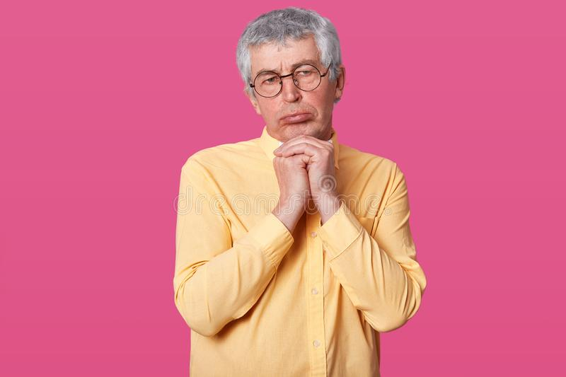Naher hoher Schuss des älteren Mannes mit Falten auf Gesicht, pouty Lippen, Blicke beleidigt, zeigt die aufgebrachte Gesichtsbeha stockfotografie