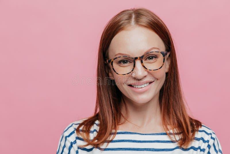 Naher hoher Schuss des attraktiver Selbstüberzeugten netten weiblichen Lehrers hat Lächeln auf Gesicht, trägt optische Gläser, tr stockfotografie