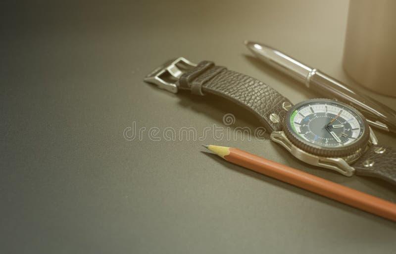 Naher hoher Schuss des Edelstahluhrgehäuses, des Lederbands mit Stift und des roten Bleistifts auf schwarzer Metalloberfläche lizenzfreie stockfotos