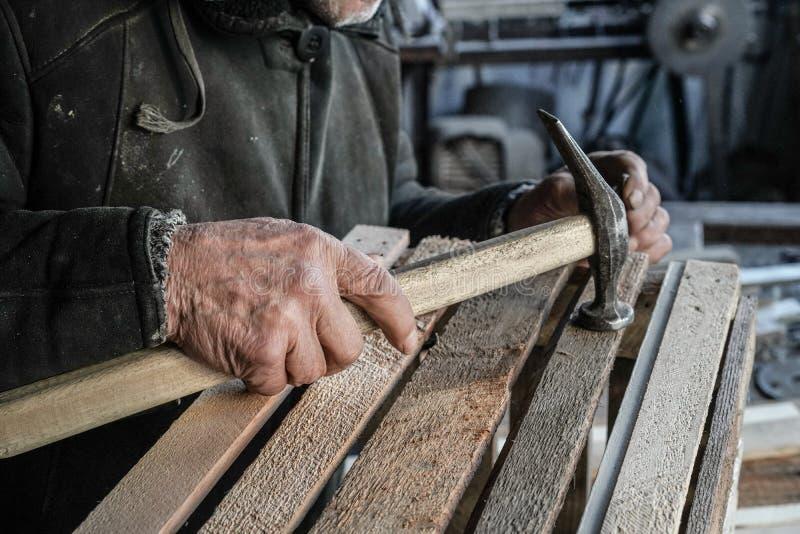 Naher hoher Schuss des Vorlagentischlers arbeitend in seiner Holzarbeit oder in Werkstatt Hammer im erfahrenen Arbeiter stockbild