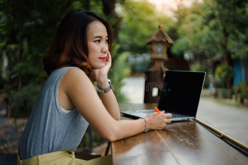 Naher hoher Schuss eines jungen weiblichen Hochschulstudenten schreibt eine Anmerkung und eine Aufgabe mit einem Laptop dazu auße lizenzfreies stockbild