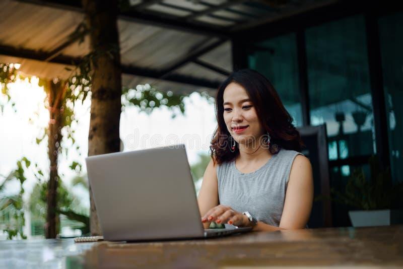 Naher hoher Schuss eines jungen weiblichen Hochschulstudenten schreibt eine Anmerkung und eine Aufgabe mit einem Laptop dazu auße stockbilder