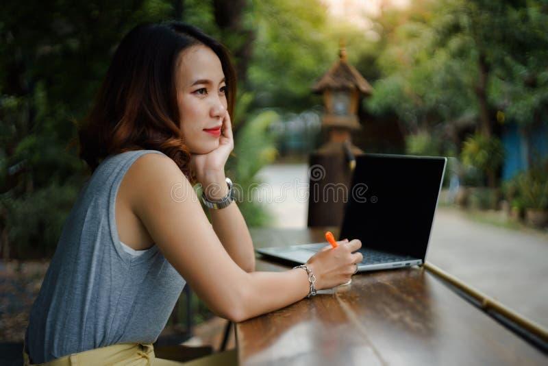 Naher hoher Schuss eines jungen weiblichen Hochschulstudenten schreibt eine Anmerkung und eine Aufgabe mit einem Laptop dazu auße stockfotos