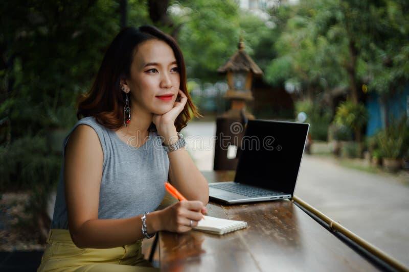 Naher hoher Schuss eines jungen weiblichen Hochschulstudenten schreibt eine Anmerkung und eine Aufgabe mit einem Laptop dazu auße lizenzfreie stockfotografie