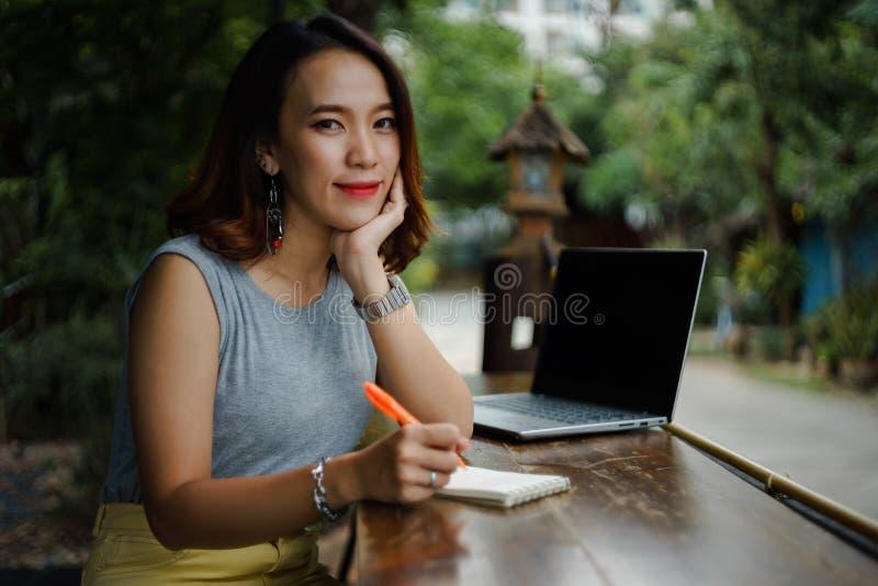 Naher hoher Schuss eines jungen weiblichen Hochschulstudenten schreibt eine Anmerkung und eine Aufgabe mit einem Laptop dazu auße lizenzfreie stockfotos