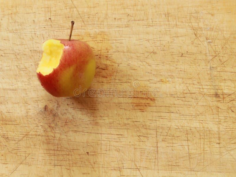 Naher oben roter Apfel mit einem Biss auf einem h?lzernen Brett von oben lizenzfreies stockfoto