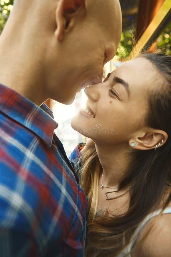 Nahes hohes Bild des glücklichen Paars in der Liebe, Spaß habend und lachen im Park Junger Mann, der Frau mit Sonnenstrahlen küss lizenzfreies stockbild