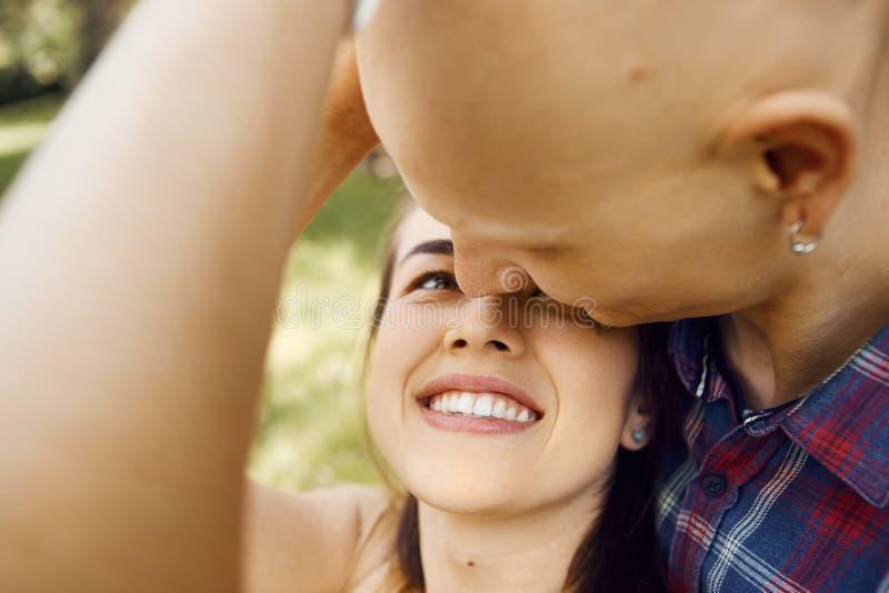 Nahes hohes Bild von den jungen Paaren, die Spaß haben und im Park lachen Freund umarmt seine Freundin von hinten lizenzfreie stockbilder