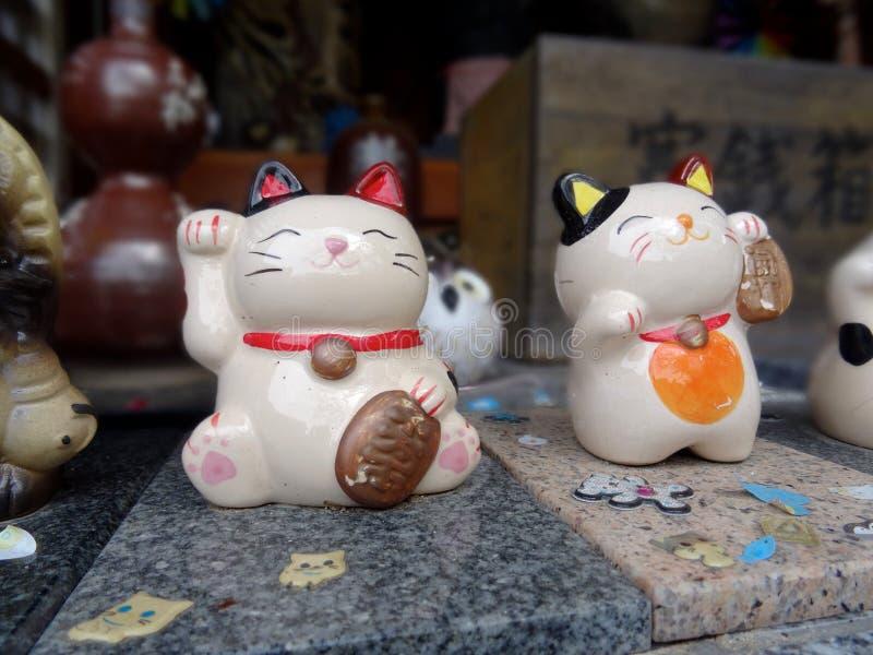 Nahes hohes Bild von zwei Maneki-Nekozahlen lizenzfreie stockfotos