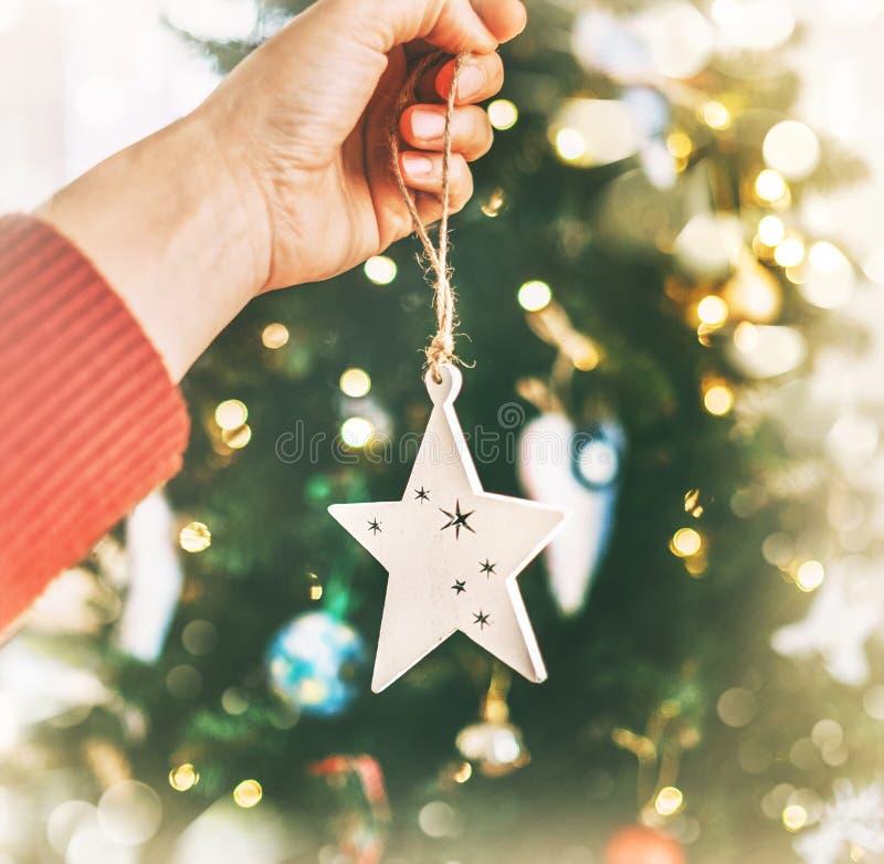 Nahes hohes Bild weibliche Handder hängenden Weihnachtshölzernen Sterndekoration auf geziertem Baum Unfocused grünes Niederlassun lizenzfreie stockfotografie