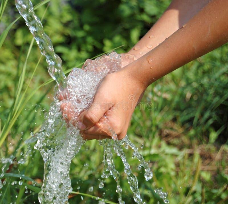 Nahes hohes des Handanziehendes sauberes fallendes Wassers lizenzfreies stockbild