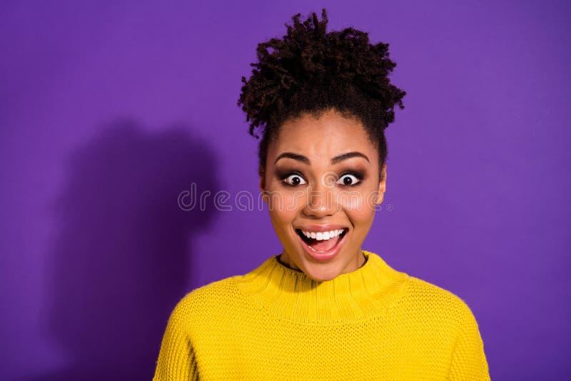 Nahes hohes Foto des netten Jugendpersonenblickes, der erstaunt wird, tragen die helle Strickjacke, die über violettem Hintergrun lizenzfreie stockfotografie