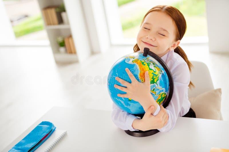 Nahes hohes Foto des reizend netten reizenden Kindes, das nahe Augen Aufgabenwissenschaft schulen mögen, kleidete weiße Hemdbluse lizenzfreies stockbild