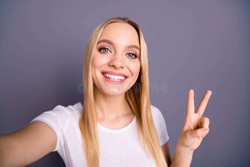 Nahes hohes Foto reizend attraktiver netter netter Dame lassen Vzeichen Fotos positive nette lange Frisurfrisur sich freuen lizenzfreies stockbild