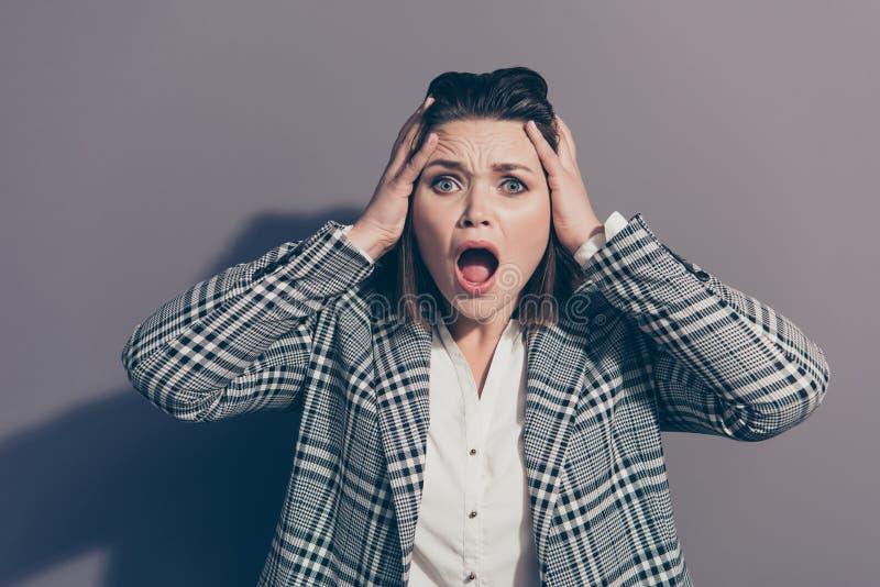 Nahes hohes Fotoporträt von nervösem unglücklichem mit offener Munddame, die sich berührt, Kopf mit den Händen halten, lokalisier stockfoto