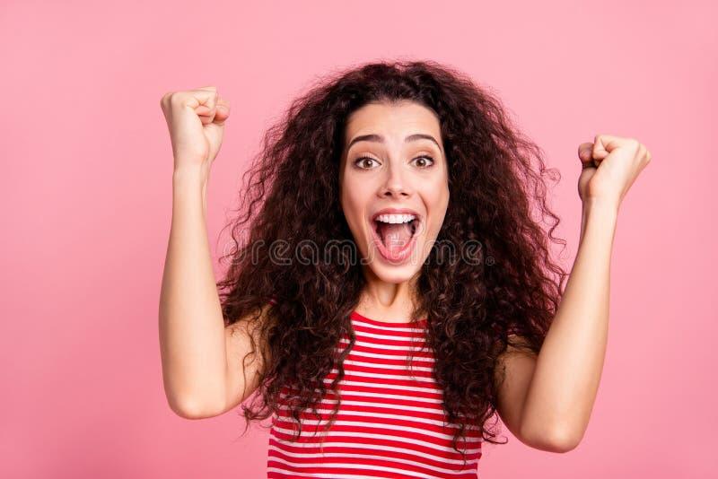 Nahes hohes Fotoporträt von nettem positivem optimistischem kühlem mit dem offenen Mund, der sie Dame oben anhebt Fausthände ihre lizenzfreie stockfotografie