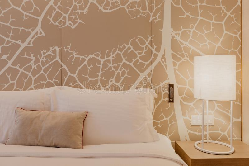 Nahes hohes Fragment des Schlafzimmers mit Leselampe im modernen Haus oder im Hotel stockfotografie