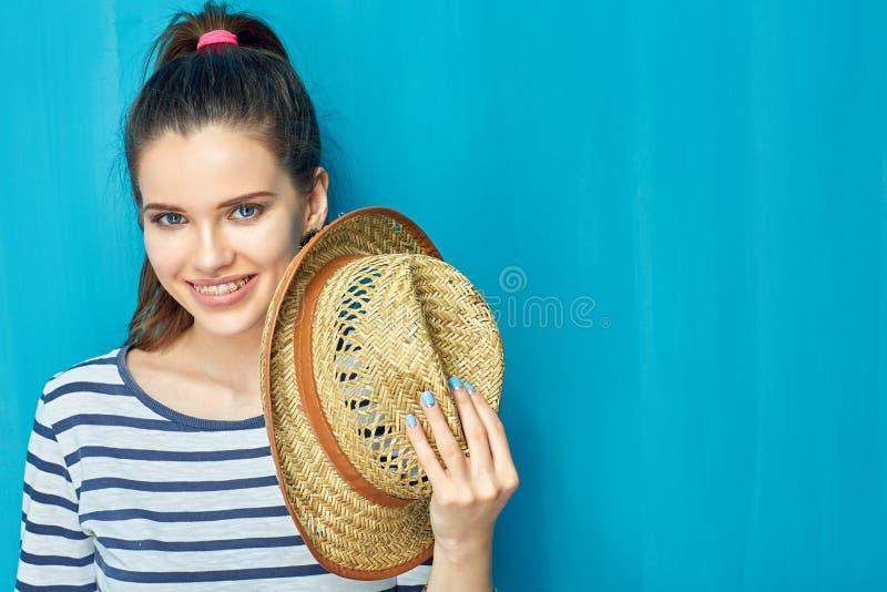 Nahes hohes Gesichtsporträt des lächelnden jugendlich Mädchenholdinghutes lizenzfreie stockfotografie
