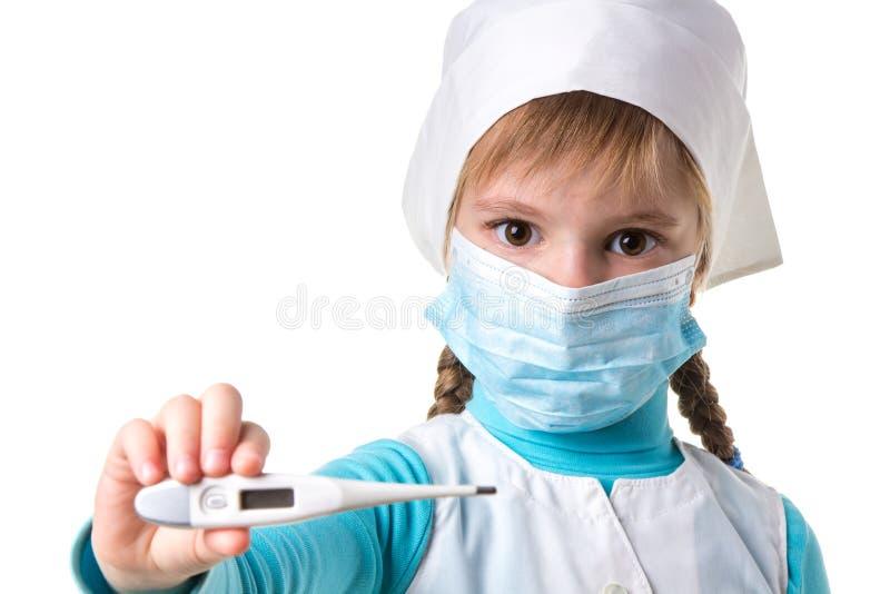 Nahes hohes Landschaftsfoto der jungen Ärztin mit der madical Maske, die elektronischen Thermometer in der rechten Hand hält stockfotografie