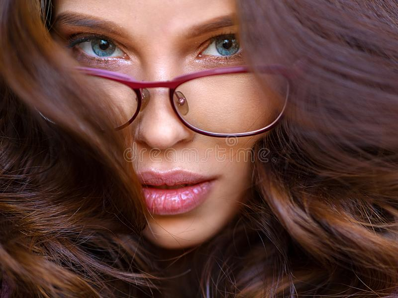 Nahes hohes Modeporträt des hübschen Mädchens, haben lang die erstaunlichen Kraushaare und tragen Weinlesesonnenbrille stockfotografie