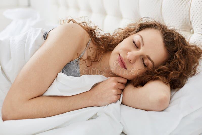 Nahes hohes Morgenporträt der attraktiven jungen sinnlichen Frau, die auf weißes Bett legt, schließen ihre Augen, hat Frau langes stockbild