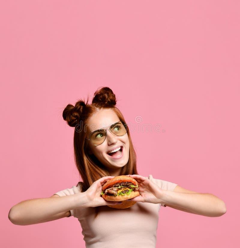 Nahes hohes Porträt einer hungrigen jungen Frau, die den Burger lokalisiert über weißem Hintergrund isst stockbilder