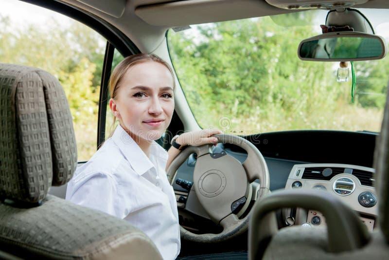 Nahes hohes Porträt der angenehmen schauenden Frau mit frohem positivem Ausdruck, mit dem Auto stellend mit unvergesslicher Reise stockfoto