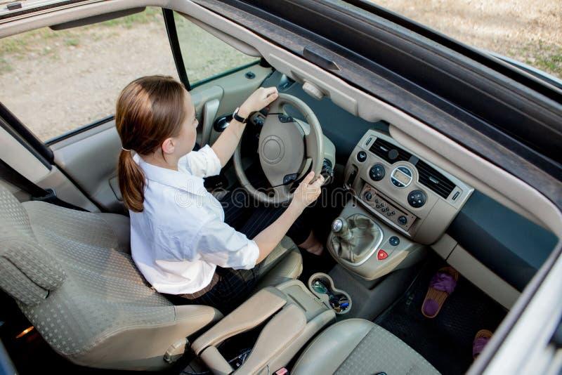 Nahes hohes Porträt der angenehmen schauenden Frau mit frohem positivem Ausdruck, mit dem Auto stellend mit unvergesslicher Reise lizenzfreie stockbilder