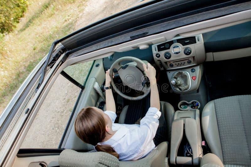 Nahes hohes Porträt der angenehmen schauenden Frau mit frohem positivem Ausdruck, mit dem Auto stellend mit unvergesslicher Reise stockfotografie