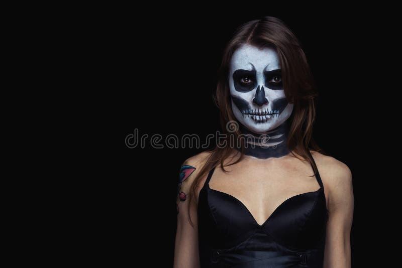 Nahes hohes Portr?t der braunhaarigen Frau mit Halloween-Sch?del bilden ?ber schwarzem Hintergrund lizenzfreie stockfotografie
