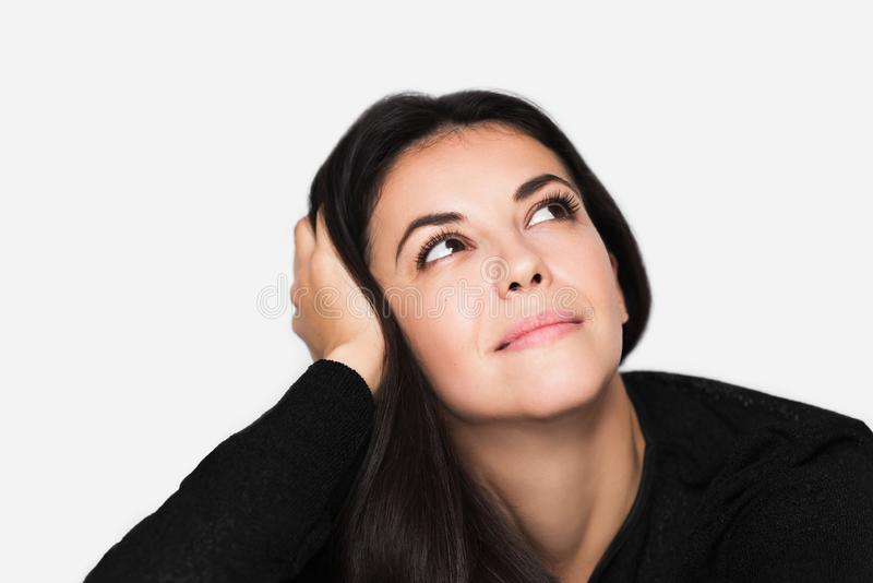 Nahes hohes Porträt der brunette netten träumerischen Frau mit der Hand auf Haar, schauen oben stockbild