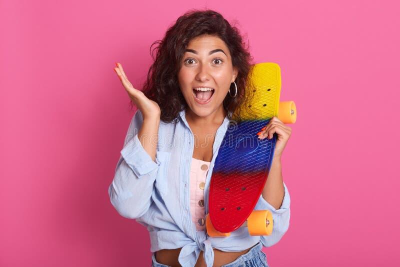 Nahes hohes Porträt der emotionalen schönen Frau, die rosa Spitzen- und blaues Hemd, eine Hand anhebend trägt und halten helles S lizenzfreie stockbilder