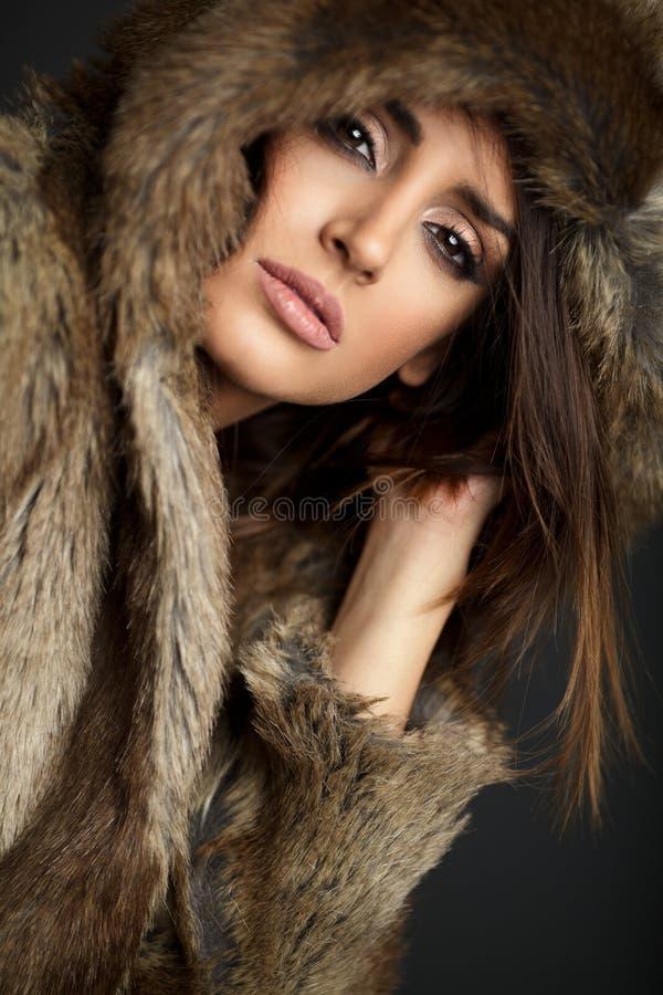 Nahes hohes Porträt der Frau einen Pelzmantel tragend, der im Studio aufwirft stockfoto
