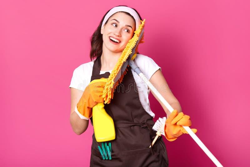 Nahes hohes Porträt der Hausfrau mit guter Laune, möchte ihr, Haus zu säubern beginnen, hat angenehme Gesichtsausdrücke, hält gel lizenzfreie stockfotografie