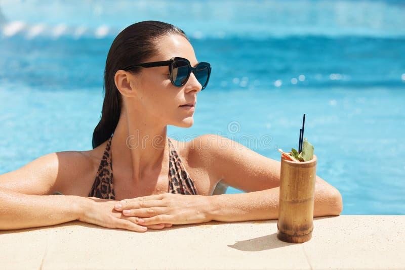 Nahes hohes Porträt der jungen Frau im Badeanzug mit dem Leoparddruck, der mit neuer Getränkstellung nahe Poolsidefreien sich ent stockbilder