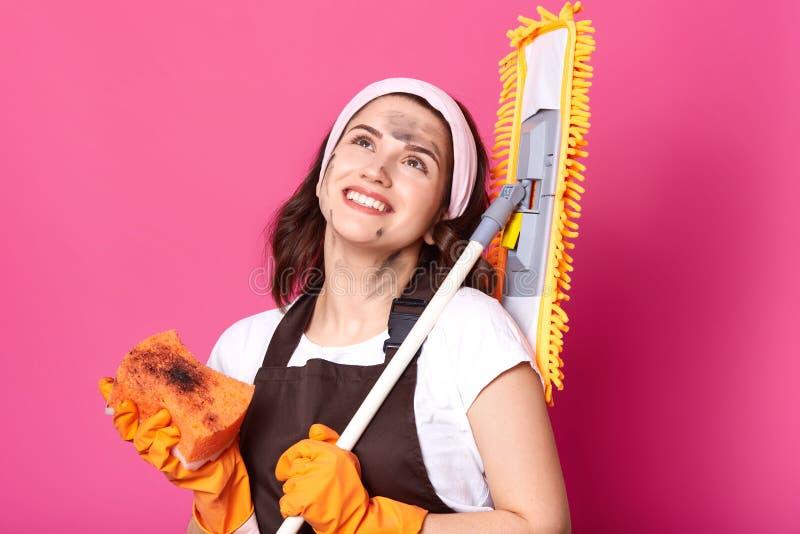Nahes hohes Porträt der lächelnden glücklichen Hausfrau, die oben, Besen und Schwamm in beiden Händen mit Handschuhen halten scha lizenzfreie stockbilder